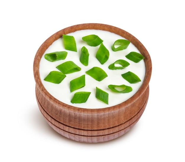 Zure room en groene ui in houten die kom op witte achtergrond wordt geïsoleerd