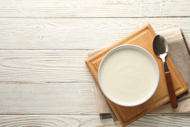 Zure roomyoghurt, lepels en servet op witte houten achtergrond