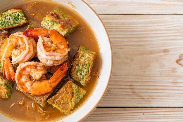 Zure soep gemaakt van tamarinde pasta met garnalen en groente omelet, aziatisch eten