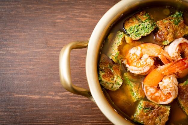 Zure soep gemaakt van tamarindepasta met garnalen en groenteomelet, aziatisch eten