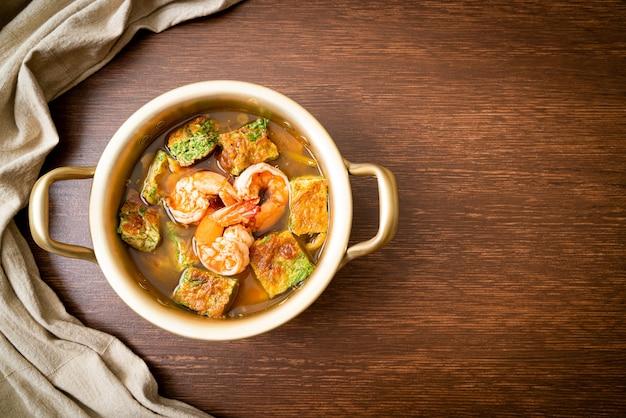 Zure soep gemaakt van tamarindepasta met garnalen en groenteomelet - aziatisch eten