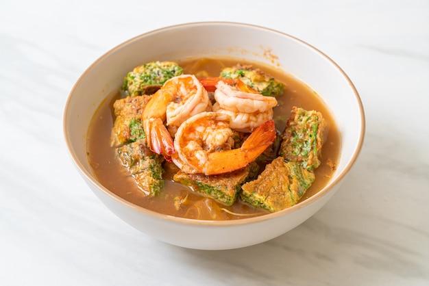 Zure soep gemaakt van tamarindepasta met garnalen en groenteomelet