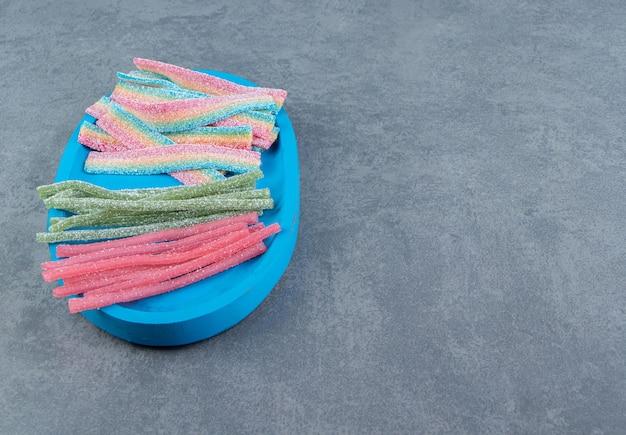 Zure taai snoepjes op blauwe plaat. Gratis Foto