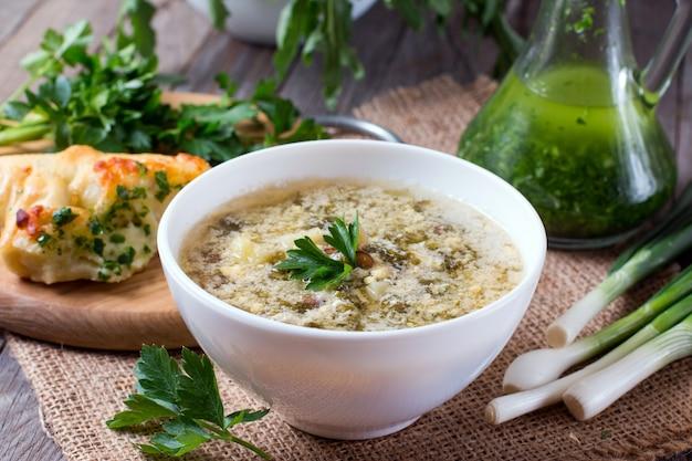 Zuring soep met ei en greens in een bord