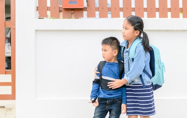 Zus en broer die schoolbus kijken