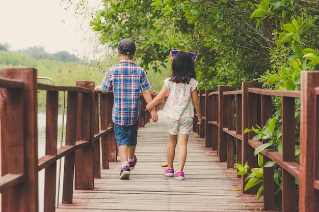 Zus en broer hand in hand lopen samen in houten brug