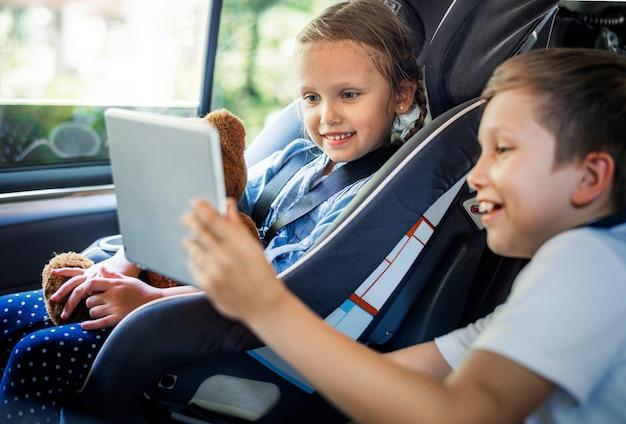Zus en broer spelen met digitale apparaten in de auto