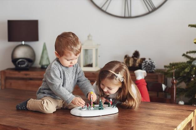 Zus en broer spelen met keramische beeldjes voor kerstmis
