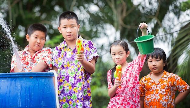 Zus en broers spelen waterpistool op het songkran-festival