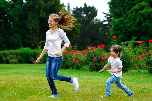Zus en kleine broer die op gras het glimlachen lopen.