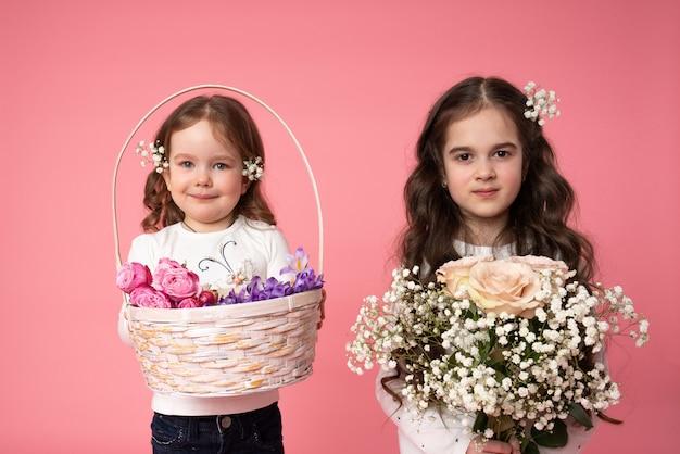 Zusjes met bloemen in hun gekrulde haire houden boeket en mand in hun handen en kijken naar de camera, lente schoonheid portret