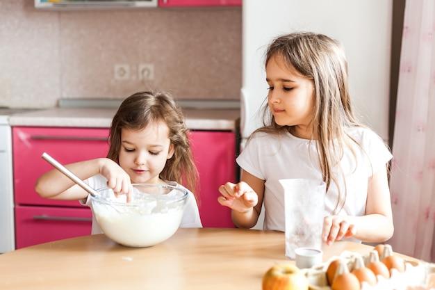 Zusters bereiden ontbijt, gebak, mix bloem, melk, eieren, pannenkoeken in een kom, kinderen helpen moeder, familie ontbijt, koken