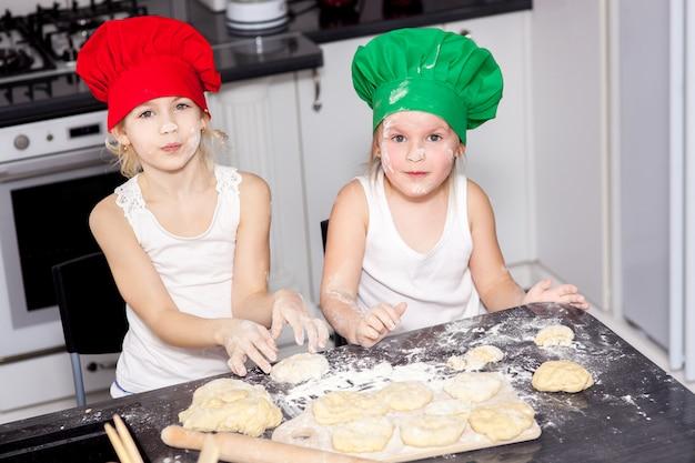 Zusters die in heldere kokhoeden samen in een keuken bakken
