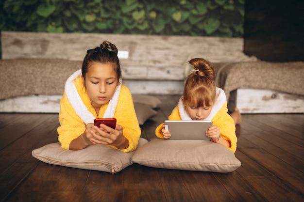 Zusters die op vloer met telefoon en tablet liggen