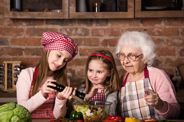 Zusters helpen oma met het bereiden van salade