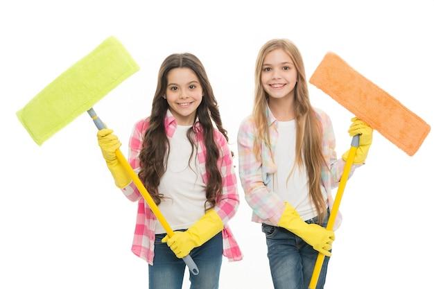 Zusters houden natte dweilen klaar om de schoonmaakdag te beginnen. meisjes schattige kinderen rond schoonmaken. hou het schoon. behulpzame vrolijke kinderen die samen schoonmaken. meisjes met beschermende handschoenen en dweilen klaar voor reiniging.
