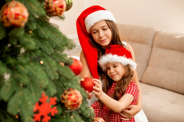Zusters kerstboom thuis versieren