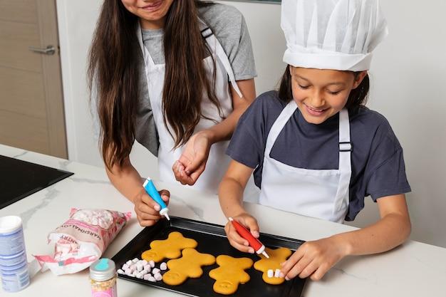 Zusters koken in de keuken met hun vader Gratis Foto