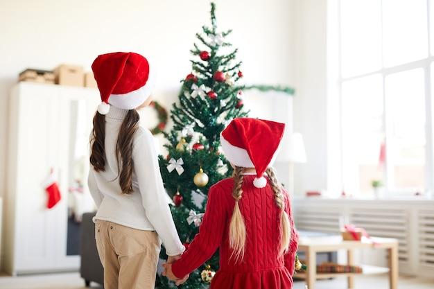 Zusters meisjes kijken naar kerstboom, interieur woonkamer