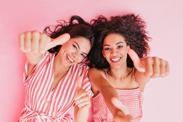 Zusters met een afrikaans uiterlijk en donker krullend haar rusten uit en laten zien dat ze allemaal super zijn met hun duimen omhoog.