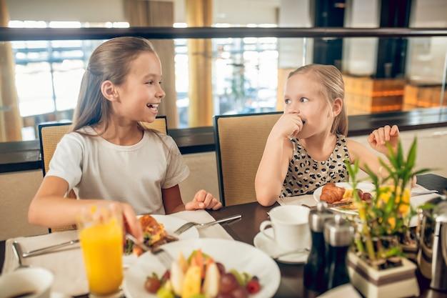 Zusters. schattige broers en zussen zitten aan de tafel en ontbijten