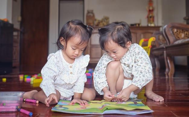 Zusters spelen thuis met knutselboek met sticker