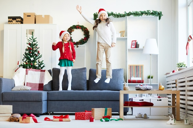 Zusters springen en spelen op de bank, meisjes met kerstmuts