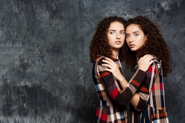 Zusters tweeling in jurken poseren op grijs
