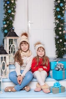 Zusters zitten op de veranda van het huis voor kerstmis