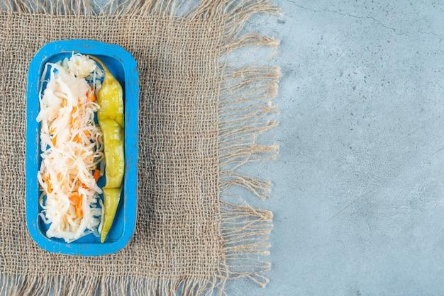 Zuurkool en ingeblikte hete peper op een houten plaat op textuur, op de marmeren tafel.