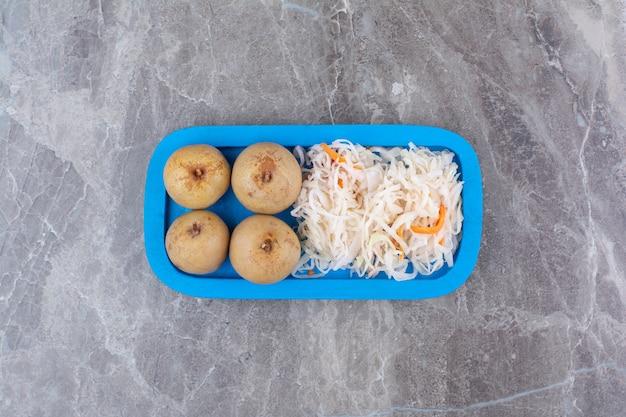 Zuurkool en ingelegde vruchten op blauw bord.