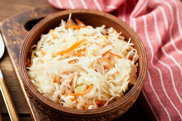 Zuurkool gefermenteerde kool met wortelen in kom op houten achtergrond close-up superfoods ter ondersteuning van het immuunsysteem