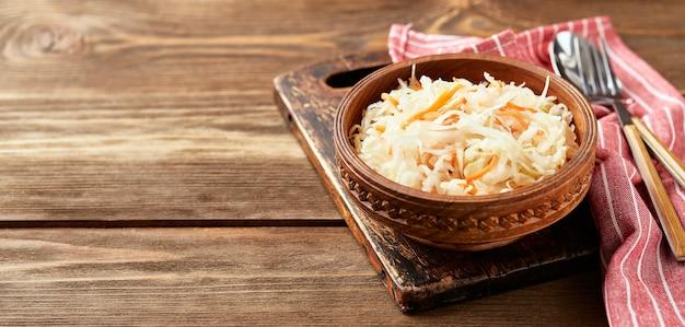 Zuurkool, gefermenteerde kool met wortelen in kom op houten achtergrond met exemplaarruimte. superfoods ter ondersteuning van het immuunsysteem.