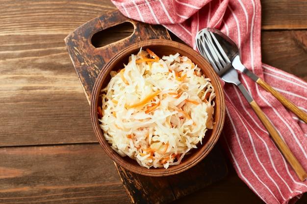 Zuurkool gefermenteerde kool met wortelen in kom op houten achtergrond superfoods ter ondersteuning van het immuunsysteem bovenaanzicht plat leggen
