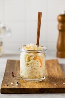 Zuurkool in een glazen pot met een vork op een houten plank fermentatie en inblikken van groenten