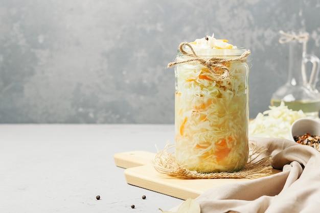 Zuurkool in een glazen pot met ingrediënten op beton met kopie ruimte.