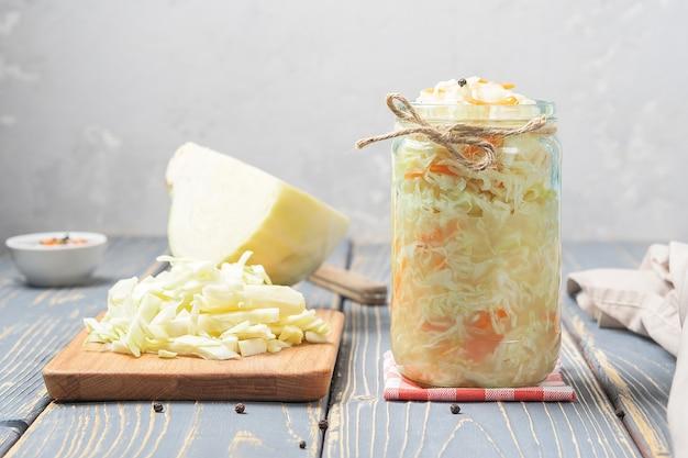 Zuurkool in een glazen pot met ingrediënten op een houten bord.