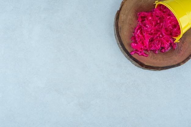Zuurkool in een omgevallen emmer op een bord, op het marmer.