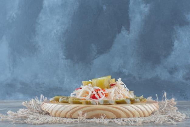 Zuurkool met augurk plakjes op houten plaat over zak