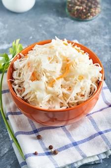 Zuurkool met kruiden in een oranje kom. natuurlijke probiotica, gezonde voeding