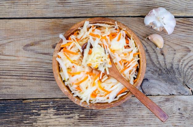 Zuurkool met wortelen in houten kom op tafel