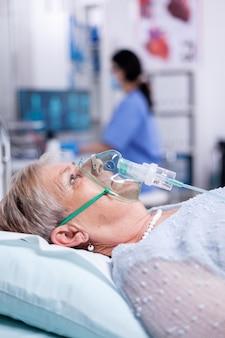 Zuurstofmasker helpt oude vrouw ademen terwijl ze in ziekenhuisbed ligt vanwege infectie met coronavirus