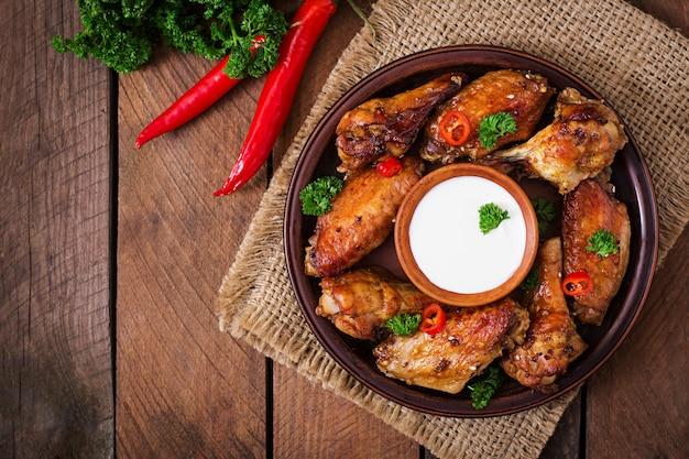 Zuurzoete gebakken kippenvleugels en saus. bovenaanzicht