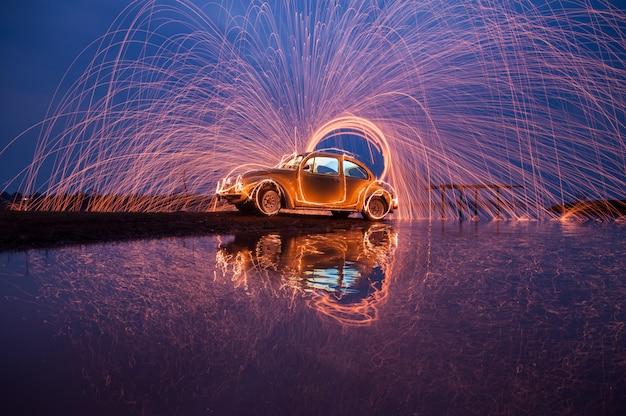 Zwaai staalwolvuur op een auto en zeewaterreflectie