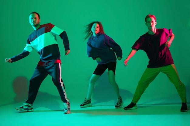 Zwaaien. stijlvolle mannen en vrouwen dansen hiphop in lichte kleding op groene achtergrond in de danszaal in neonlicht. jeugdcultuur, beweging, stijl en mode, actie. modieus portret.