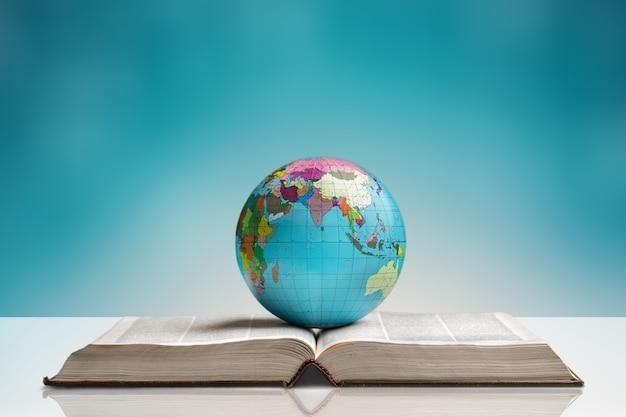Zwaar boek en wereldbol op achtergrond