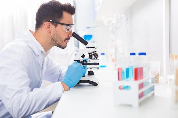 Zwaar werk. ambitieuze, gefocuste mannelijke laboratorian die in de microscoop kijkt terwijl hij in profiel poseert en zich kleedt in laboratoriumjas