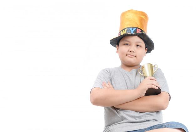 Zwaarlijvig dik kind dat gouden winnende kop houdt
