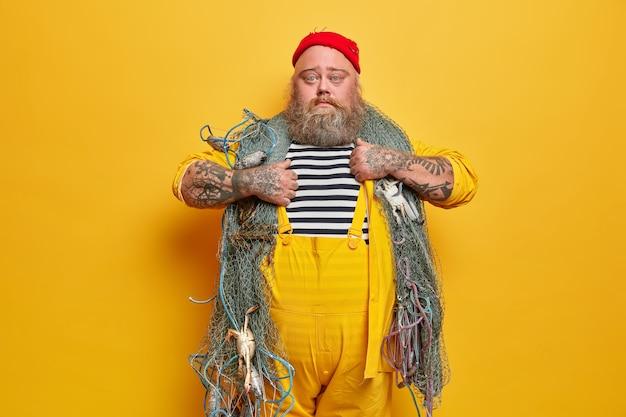 Zwaarlijvige bebaarde mannelijke matroos met visnet