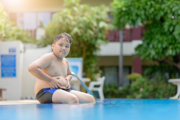 Zwaarlijvige dikke jongen zit op zwembad
